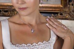 Belle jeune mariée dans la robe de mariage portant un collier Photographie stock libre de droits