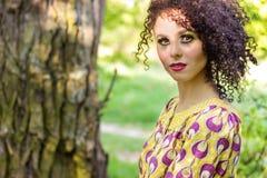 Belle jeune petite fille aux cheveux frisés avec le maquillage dans le soleil d'été le jour se reposant sur la rue Image libre de droits