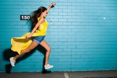 Belle jeune pose sexy de fille de hippie, souriant, surhomme volant près du fond bleu urbain de mur Photographie stock libre de droits