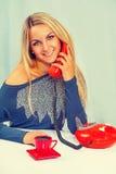 Belle jeune séance femelle de sourire près de la table et du speaki Photos libres de droits