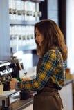 Belle jeune serveuse faisant le café utilisant une machine professionnelle dans un café Images libres de droits