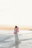 Belle jeune seule fille à la mer avec l'oiseau rose sur le coucher du soleil Photo stock