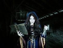 Belle jeune sorcière de Halloween lisant le livre magique et se tenir Photos stock