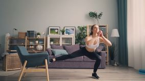 Belle jeune sportive faisant des postures accroupies à la maison utilisant le corps de formation de fauteuil clips vidéos