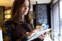 Belle jeune vendeuse à l'aide de son comprimé numérique dans la boutique organique images libres de droits