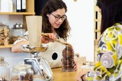 Belle jeune vendeuse pesant des biscuits de chocolat à un magasin organique Photo libre de droits
