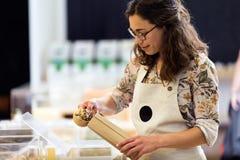 Belle jeune vendeuse prenant des pâtes d'un panier dans un magasin organique Photographie stock