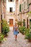 Belle jolie femme marchant à la vieille rue de trottoir de ville avec des fleurs et regardant loin concept de course Photographie stock libre de droits