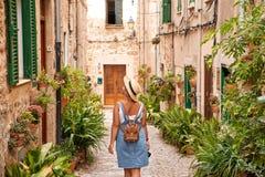Belle jolie femme marchant à la vieille rue de trottoir de ville avec des fleurs et regardant loin concept de course Photo stock