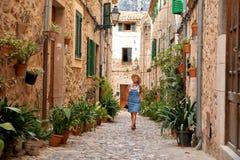 Belle jolie femme marchant à la vieille rue de trottoir de ville avec des fleurs et regardant loin concept de course Image libre de droits