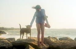 Belle jolie fille marchant avec le chien sur la plage image libre de droits