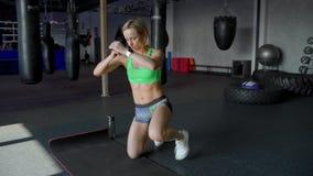 Belle la fille forte et convenable dans un dessus sportif fait des exercices accroupis dans le gymnase de boxe banque de vidéos