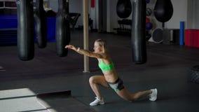 Belle la fille forte et convenable dans un dessus sportif fait des exercices accroupis dans le gymnase de boxe clips vidéos