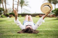 Belle, la jeune femme fixe sur l'herbe et tenir son chapeau et faire des gestes la paix photo libre de droits