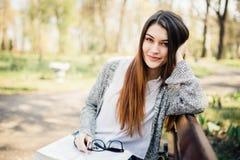 Belle lecture d'étudiant au parc sur le banc photographie stock