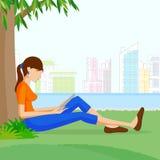 Belle lecture de femme se reposant sous l'arbre Photographie stock