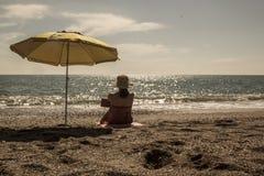 Belle lecture de femme sur la plage Image stock