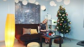 Belle lettre d'écriture de femme sur Noël se reposant sur le sofa près de l'arbre de Noël clips vidéos