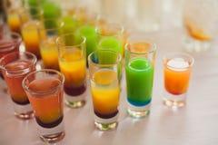 Belle ligne de différents cocktails colorés d'alcool avec de la fumée sur une fête de Noël, une tequila, un martini, une vodka, e Photographie stock