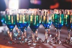 Belle ligne de différents cocktails colorés d'alcool avec de la fumée sur une fête de Noël, une tequila, un martini, une vodka, e Photos libres de droits