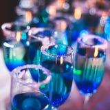 Belle ligne de différents cocktails colorés d'alcool avec de la fumée sur une fête de Noël, une tequila, un martini, une vodka, e Photo libre de droits