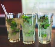Belle ligne de différents cocktails colorés d'alcool avec de la fumée sur une fête de Noël, une tequila, un martini, une vodka, e Photographie stock libre de droits