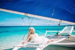 Belle longue jeune mariée blonde de cheveux dans la robe blanche Elle s'étendent sur le voilier bleu Mer de ciel bleu et de turqu Photo stock
