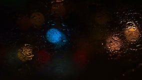 Belle lumière trouble colorée du trafic dehors sur la route Écoulements et essuie-glace de pluie sur le verre de pare-brise avant banque de vidéos