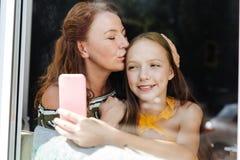 Belle mère affectueuse embrassant sa fille affectueuse Photos libres de droits