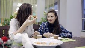 Belle mère avec sa fille mangeant de la pizza et parlant gaiement banque de vidéos