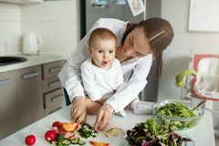 Belle mère d'une chevelure foncée faisant cuire le dîner devant son petit fils adorable Enfant regardant de côté avec amezed Images stock
