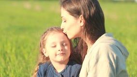 Belle mère de sourire embrassant sa fille mignonne avec le jaune banque de vidéos