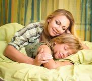 Belle mère de sourire heureuse embrassant sa fille mignonne dormant dans le lit Images stock