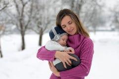 Belle mère et bébé garçon mignon dans l'onesie tricoté, ayant tak photographie stock