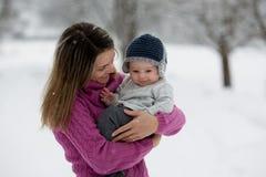 Belle mère et bébé garçon mignon dans l'onesie tricoté, ayant tak images stock