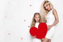 Belle mère et fille blondes de femme se tenant sur un fond blanc et tenant un coeur rouge Image libre de droits