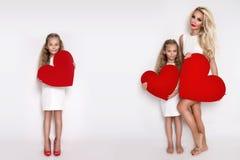 Belle mère et fille blondes de femme se tenant sur un fond blanc et tenant un coeur rouge Photos libres de droits