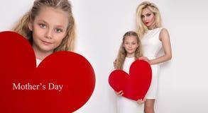 Belle mère et fille blondes de femme se tenant sur un fond blanc et tenant un coeur rouge Photographie stock