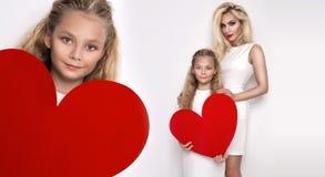 Belle mère et fille blondes de femme se tenant sur un fond blanc et tenant un coeur rouge Image stock