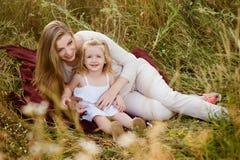 Belle mère et fille de sourire blondes enceintes étreignant, valeurs familiales, amour Photo stock
