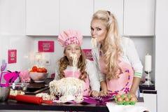 Belle mère et fille renversantes de femme dans la cuisine de tabliers faisant cuire dans les biscuits de cuisine image libre de droits