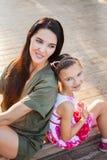 Belle mère et fille s'asseyant dehors sur des étapes et laughting Photographie stock libre de droits