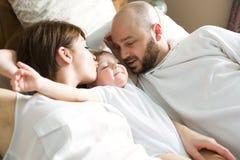 Belle mère et père beau avec la fille de bébé se trouvant sur la chambre à coucher Images libres de droits