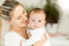 Belle mère gaie embrassant ses 3 mois de bébé garçon Images stock