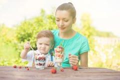 Belle mère heureuse et son garçon d'enfant mangeant le dessert posé dans le jardin vert dans le jour d'été ensoleillé Image libre de droits