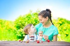 Belle mère heureuse et son garçon d'enfant mangeant le dessert posé dans le jardin vert dans le jour d'été ensoleillé Photos libres de droits