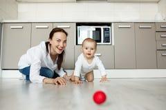 Belle mère joyeuse et petit fils de bébé avec de grands yeux bruns jouant ainsi que la boule rouge dans la cuisine Scène de Images libres de droits