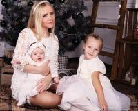 Belle mère posant avec ses filles mignonnes posant près de l'arbre de Noël Photo libre de droits