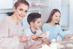 Belle mère souriant tout en prenant le petit déjeuner avec la famille Image stock