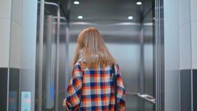 Belle Madame appelle l'ascenseur en appuyant sur le bouton, en entrant dans et en fermant des portes clips vidéos